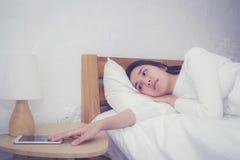 Main de femme somnolente se réveillant avec le réveil au téléphone portable Image stock