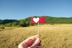 Main de femme stockant le texte d'amour sur le bâton Fin vers le haut Images libres de droits