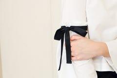 Main de femme sur la longue douille blanche avec les détails noirs de style de noeud papillon de ficelle Fermez-vous vers le haut Images stock