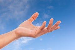 Main de femme sur le ciel Image stock