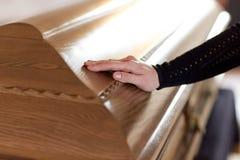 Main de femme sur le couvercle de cercueil à l'enterrement dans l'église photo stock