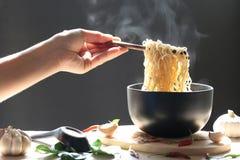 Main de femme tenant des baguettes des nouilles instantanées dans la tasse avec le smo image stock