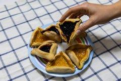 Main de femme tenant des biscuits de confiture de myrtille et d'abricot de Hamantash Purim de plat color? sur la nappe bleue et b images libres de droits