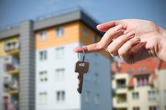 Main de femme tenant des clés sur la nouvelle maison Image stock