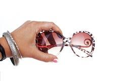Main de femme tenant des lunettes de soleil sur le fond blanc d'isolement de coupe-circuit Photo de studio avec l'allumage de stu Photo libre de droits