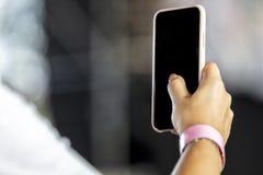 Main de femme tenant dessus le téléphone portable avec le fond brouillé image libre de droits