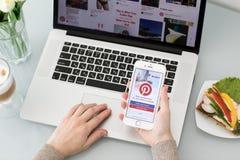 Main de femme tenant l'iPhone avec le service Internet social Pinterest Images stock