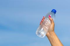 Main de femme tenant la bouteille d'eau dehors Image libre de droits