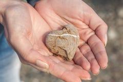 Main de femme tenant la forme en pierre du coeur Photos stock