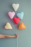 Main de femme tenant la forme multicolore de coeur de ballons sur le mur bleu Photographie stock