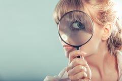 Main de femme tenant la loupe sur l'oeil Photographie stock libre de droits
