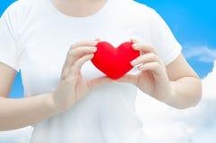 Main de femme tenant la peluche un coeur rouge à la gauche son coffre sur le fond de ciel bleu Photographie stock libre de droits