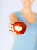 Main de femme tenant la pomme rouge avec la forme de coeur Images stock