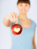 Main de femme tenant la pomme rouge avec la forme de coeur Photos stock