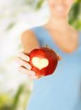 Main de femme tenant la pomme rouge avec la forme de coeur Photo libre de droits