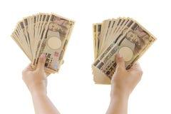 Main de femme tenant le billet de banque de 10.000 Japonais Yen Bills Isolate Photos stock