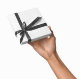 Main de femme tenant le boîtier blanc actuel de vacances avec Grey Ribbon Photo libre de droits