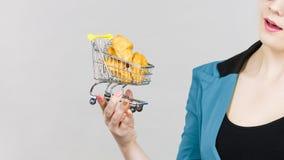Main de femme tenant le caddie avec le petit pain doux Image stock