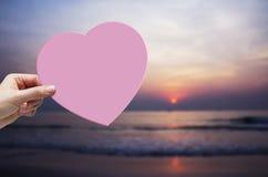 Main de femme tenant le coeur de papier rose sur la plage Photos libres de droits