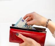 Main de femme tenant le portefeuille rouge et retirant l'argent Photos stock