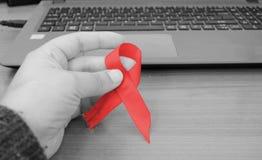 Main de femme tenant le ruban rouge pour la Journée mondiale contre le SIDA photographie stock