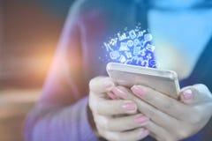 Main de femme tenant le téléphone intelligent se reliant à l'Internet et aux icônes sociales de media Image stock