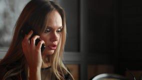 Main de femme tenant le téléphone portable blanc sur une table avec un ordinateur portable dans le bureau banque de vidéos