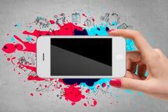 Main de femme tenant le téléphone portable sur le fond gris Photos libres de droits