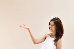 Main de femme tenant quelque chose sur l'espace vide sur le fond simple Photos stock