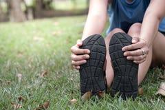 Main de femme tenant ses pieds et étirer les muscles dans la PA photo stock