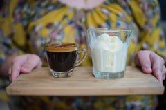 Main de femme tenant une tasse de café ou d'expresso d'Affogato avec la glace sur le conseil en bois Photographie stock libre de droits