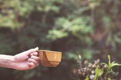 Main de femme tenant une tasse de café sur un CCB tropical de palmettes photo libre de droits