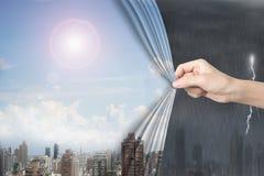 Main de femme tirant le couvert ensoleillé de rideau en paysages urbains de ciel orageux Photographie stock