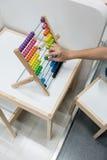 Main de femme utilisant le jouet d'abaque sur la table d'étude d'enfant Photos libres de droits
