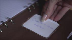 Main de femme utilisant le traqueur quotidien d'habitude de planificateur de carnet d'autocollant en cuir brun clair de protectio banque de vidéos