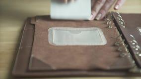 Main de femme utilisant le traqueur quotidien d'habitude de planificateur de cas de livre élégant en cuir brun clair de bloc-note banque de vidéos