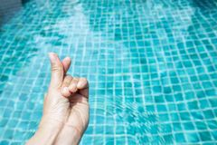 Main de fille avec le signal d'amour au-dessus de la piscine bleue Photo stock