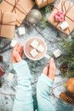 Main de fille avec les cadeaux de Noël et le chocolat chaud photographie stock