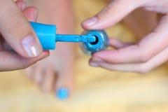 Main de fille d'adolescent avec la pédicurie de brosse de laque d'émail son pied d'orteils Photo stock