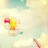 Main de fille jugeant les ballons multicolores faits avec un rétro vintage Photo stock