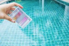 Main de fille tenant l'appareil de contrôle de piscine photos stock