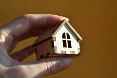 Main de fille tenant la maison miniature en bois de jouet sur la lumière du soleil avec le fond jaune photos libres de droits