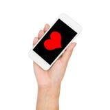 Main de fille tenant le coeur rouge d'affichage de téléphone portable sur l'écran Photographie stock