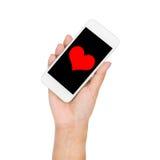 Main de fille tenant le coeur rouge d'affichage de téléphone portable sur l'écran Photo libre de droits