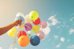 Main de fille tenant les ballons multicolores Photos libres de droits