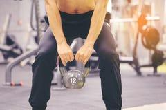 Main de formation d'homme tenant le kettlebell pour la graisse de brûlure dans le corps dans le gymnase de sport, le mode de vie  photographie stock libre de droits