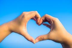Main de forme d'amour en ciel Images libres de droits