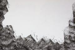 Main de fusain dessinant le cadre noir Images stock
