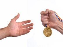 Main de gagnant de récompense tenant une médaille d'or Image stock