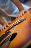 Main de garçon sur une guitare Photographie stock libre de droits